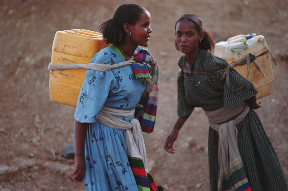 girls carry water on International Woman's Day