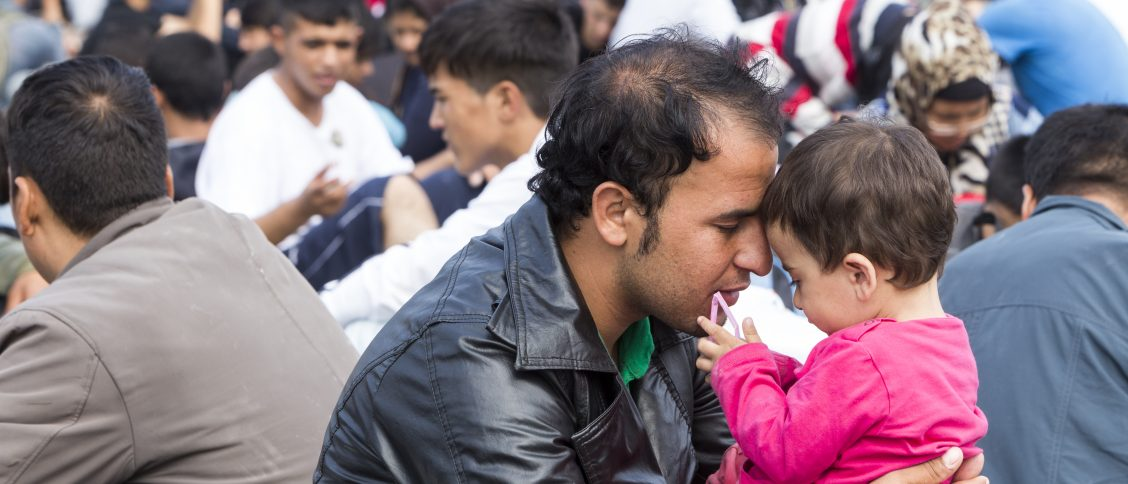 Man holds child waiting at Greek border to continue journey for asylum