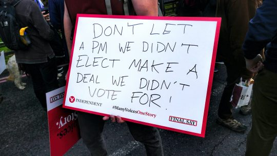 Protestor with a sign against Boris Johnson pushing through a deal we didn't vote for