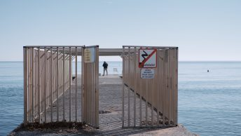 A large cage on the end of a pier looking out to sea