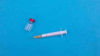 Vaccine vial and needle on blue background