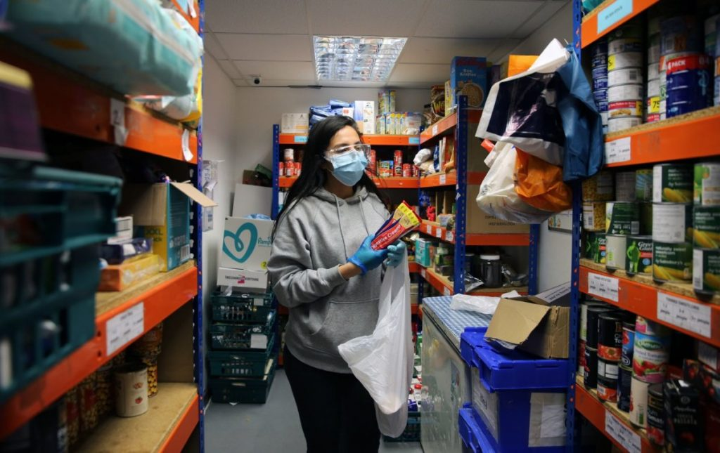 Young woman stocks foodbank shelves in a mask