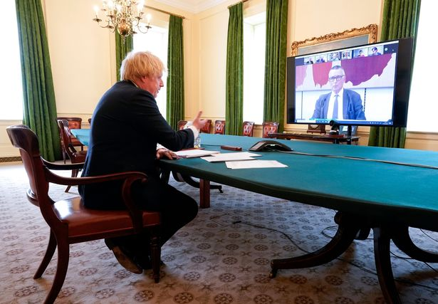 Prime Minister Boris Johnson sitting at a table at video call