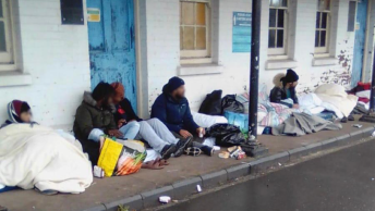 Asylum seekers sat outside protesting at UK migrant camp