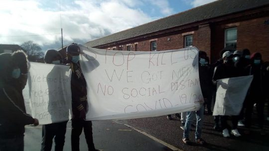 Asylum seekers detained in a UK camp hold up a sheet protesting their living conditions