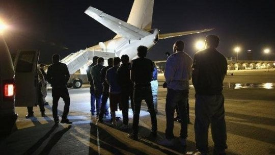 Men waiting to be put on a deportation flight