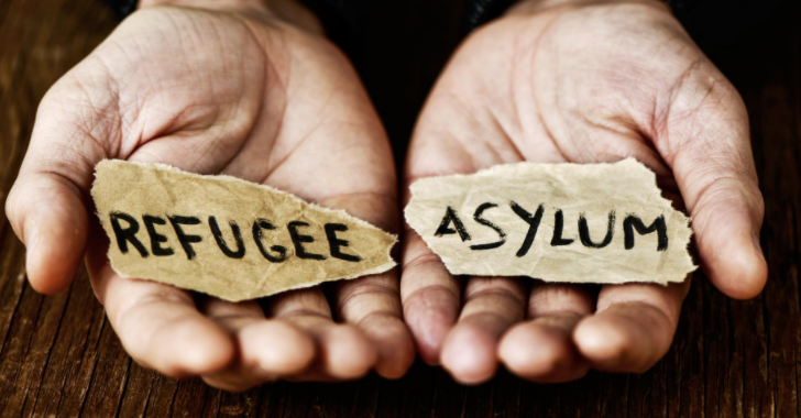 Hands holding the words refugee and asylum