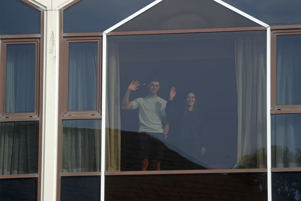 People standing at hotel window in hotel quarantine adversely affecting migrants