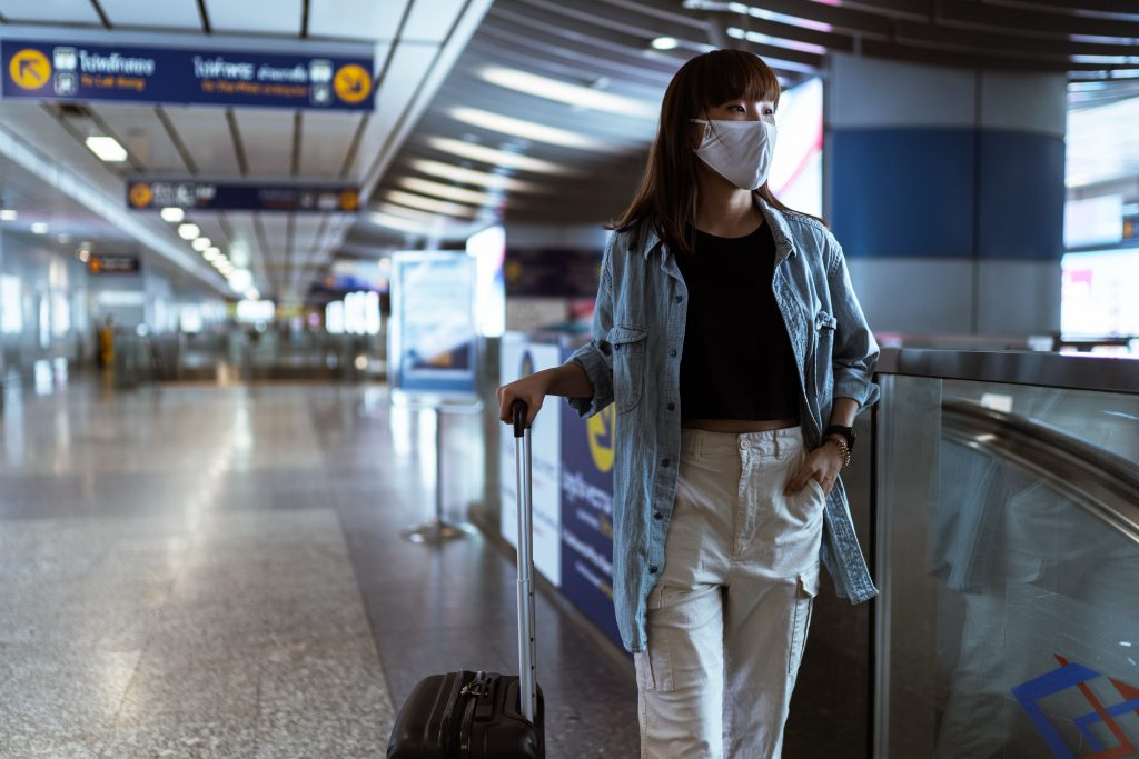 UK immigration statistics been affected by travel bans during the pandemic. Person in an airport with a mask